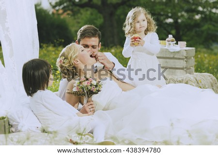 romantic boho wedding outside in green, bride and make Groom along with their two sweet flower children a romantic picnic. He tenderly feeding his bride with grapes.