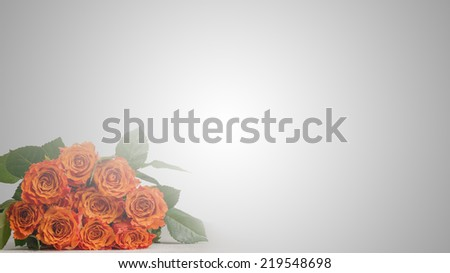 Romantic bouquet of fresh red roses with a large copyspace with a vintage flare effect graduating from white to grey for your message to a loved one. - stock photo
