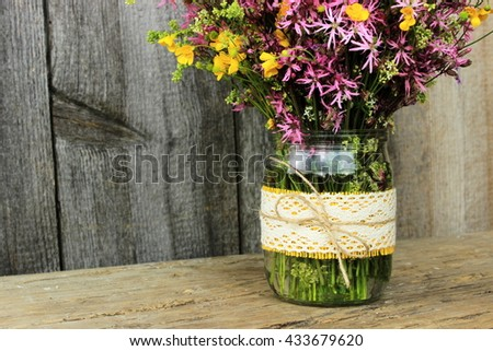 Romantic bouquet of wildflowers including yellow buttercups in a simple glass pot decorated with textile ribbon and crochet lace with jute bow in a grunge rustic setting. Vintage decor theme