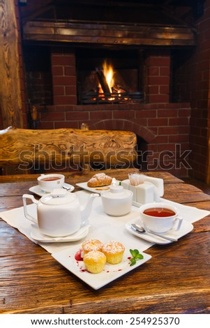 Romantic breakfast near fireplace - tea, muffin and croissant