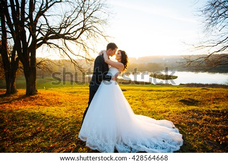 Romantic bride and groom at sunset - stock photo