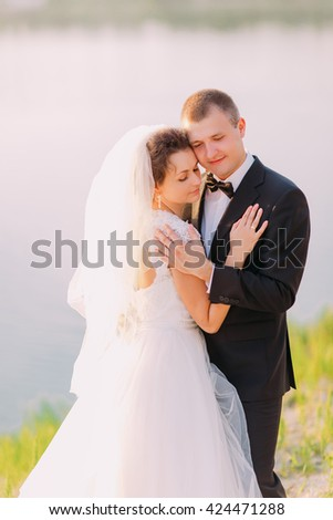 Romantic bride and groom embracing on the nature, in the background lake