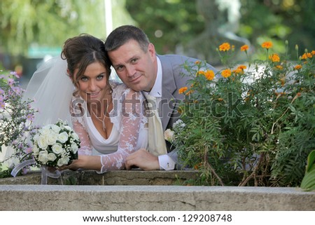 romantic bride and groom posing beside flower pots with flowers