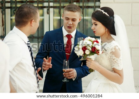 Romantic bride & groom drinking champagne outdoors, wedding celebration