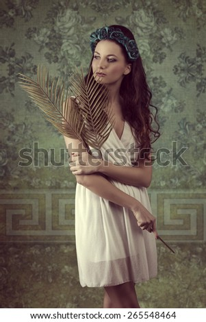 romantic brunette girl with long wavy hair posing in spring portrait with flowers on head and palm leafs in the hand. Wearing white dress  - stock photo