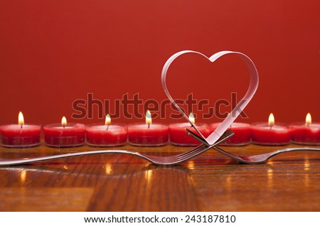 Romantic card a heart over forks with candles behind.  Valentines day  - stock photo