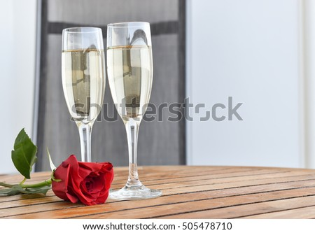 Romantic celebration setting with two glasses of sparkling wine and a red rose on a wooden table. Valentine's day concept.