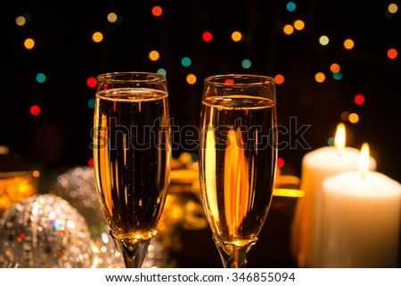 Romantic champagne in two elegant flutes to celebrate Christmas and New Year with burning candles and a background bokeh of colorful party lights
