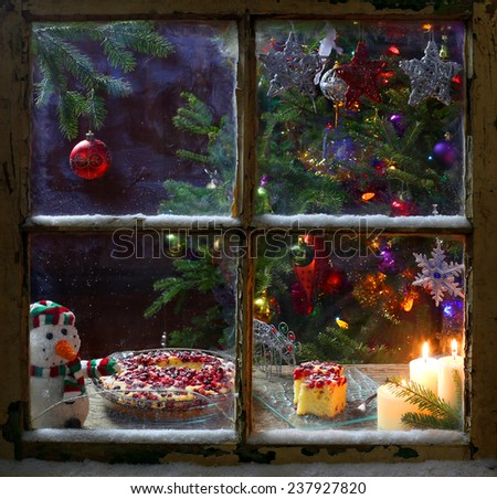 Romantic Christmas decoration on a window with candles and cake - stock photo