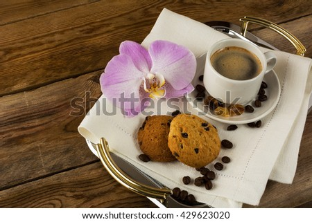 Romantic coffee served with orchid on the serving tray. Coffee break with homemade cookies. Morning coffee and breakfast cookie.     - stock photo