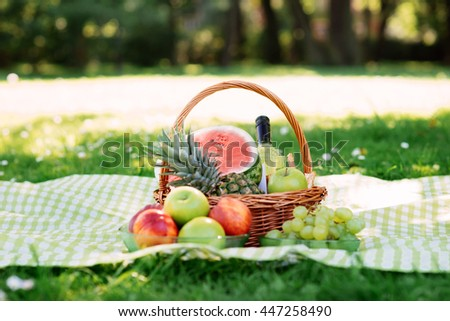 Romantic composition of basket with fruits and wine in the park.