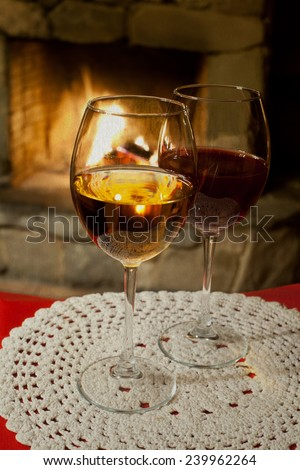 Romantic concept: Two glasses of wine. White tablecloth. Fireplace. Chimney. (vintage paper background, retro style). - stock photo
