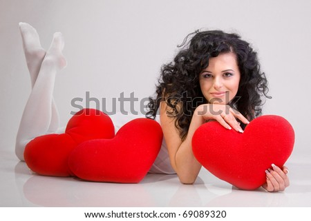 Romantic concept with girl and heart-shaped pillows - stock photo