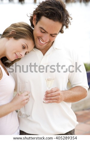 Romantic couple at a tropical hotel bar, drinking champagne - stock photo