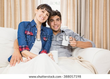 Romantic couple at home relaxing on the sofa having coffee - stock photo