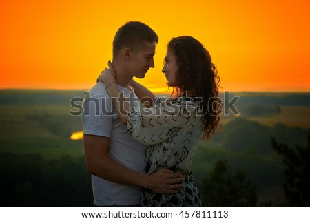 romantic couple at sunset on bright yellow sky background, love tenderness concept, young adult people