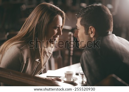 Romantic couple at the bar staring at each other's eyes - stock photo