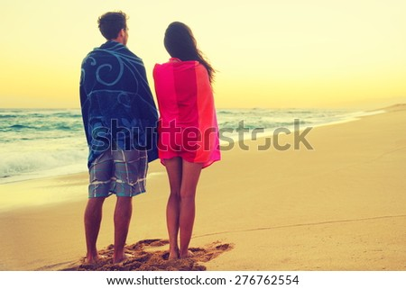 Romantic couple bathing with towels on beach sunset. Portrait of happy young couple looking at sunrise ocean sea view during holidays vacation travel. Asian woman, Caucasian man. - stock photo
