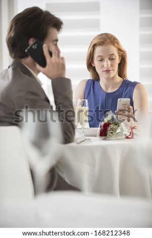 romantic couple bored together at restaurant