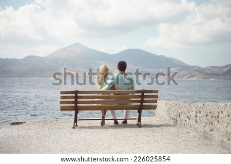 Romantic couple by the sea looking into the distance
