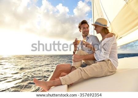 Romantic couple cheering on sailboat at sunset - stock photo
