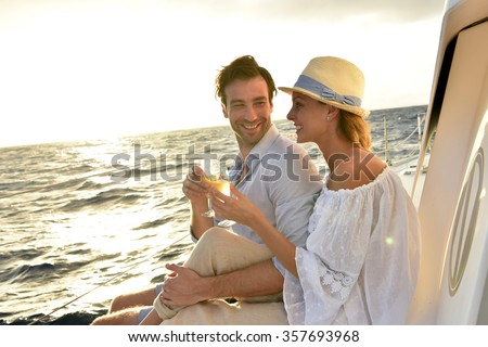 Romantic couple cheering on sailboat at sunset - stock photo