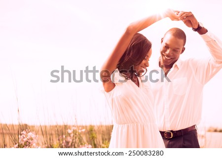 Romantic couple dancing and smiling outside in the garden - stock photo