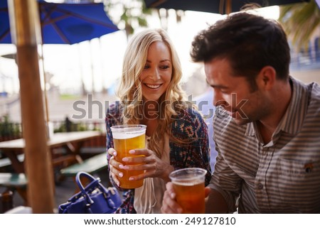 romantic couple drinking beer at outdoor restaurant - stock photo