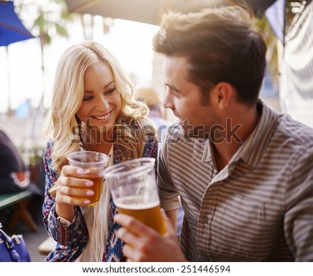 romantic couple drinking beer in plastic cups at outdoor bar - stock photo