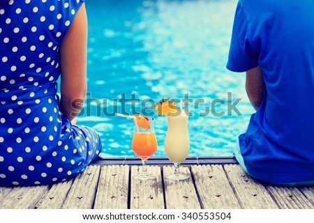 romantic couple drinking cocktails near pool or beach in luxury resort - stock photo