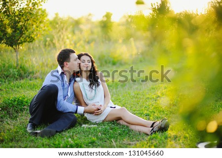 romantic couple embraces in the field