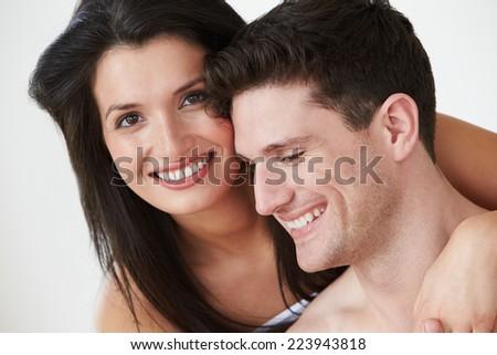 Romantic Couple Embracing Against White Studio Background - stock photo