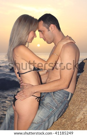 Romantic couple embracing at seaside on a sunset