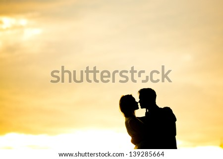 romantic couple embracing each other on background of lake at sunset - stock photo