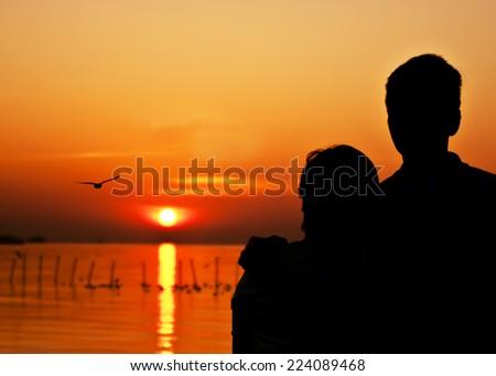 romantic couple enjoy morning sunrise - sunlight bright orange sun happiness lake sea bird horizon - silhouette concept - stock photo