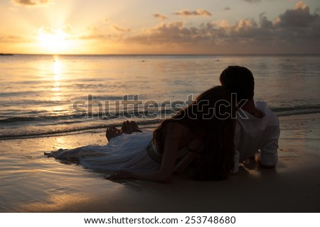 Romantic couple enjoying a beach walk at sunset. Happy Romantic Couple Enjoying Beautiful Sunset at the Beach.  - stock photo