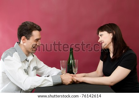 Romantic couple enjoying a meal on red burgundy background - stock photo