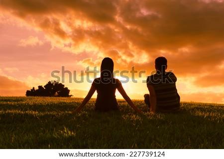 Romantic couple enjoying beautiful sunset in Hawaii - stock photo