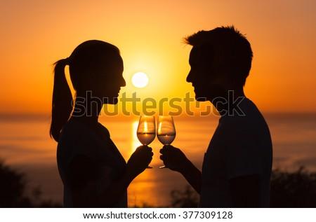 Romantic couple enjoying glass of wine against a beautiful sunset - stock photo