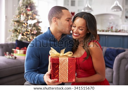 Romantic Couple Exchanging Christmas Gifts At Home - stock photo