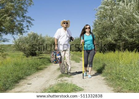 Romantic couple forty years traveling down a country road on the river bank