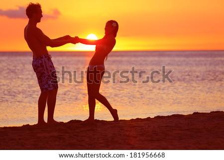 Romantic couple fun on beach sunset during travel. Happy woman and man holding hands playful on honeymoon romance in beautiful sun light. Multiracial couple, Image from Big Island, Hawaii. - stock photo