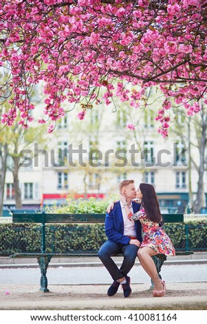 Romantic couple having a date in Paris on a spring day with beautiful cherry blossoms in the background - stock photo