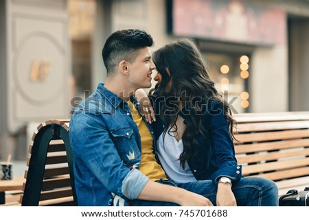 Romantic couple having fun in the city spending time together in love. young couple drinking coffee on the street. Guy and girl full of affection and romance, hugging on the city street