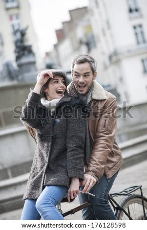 romantic couple having fun on a bicycle - stock photo