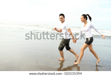 Romantic couple having fun on the beach - stock photo