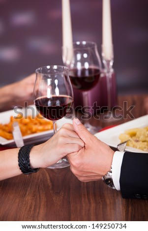 Romantic Couple Holding Each Other's Hand At Dinner In An Restaurant