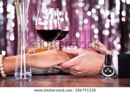Romantic Couple Holding Each Other's Hand At Dinner In An Restaurant - stock photo