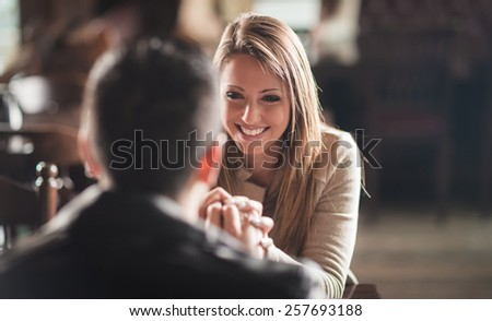 Romantic couple holding hands at the bar staring at each other's eyes - stock photo