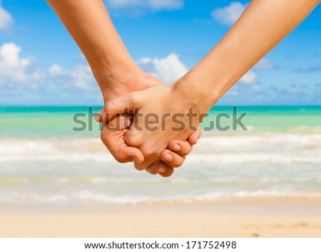 Romantic couple holding hands on the beach.  - stock photo